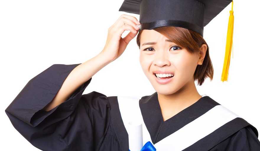 Woman in graduation cap with a confused look on her face.