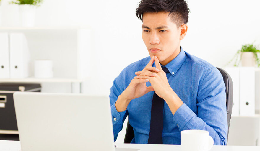 Man sitting at computer with the look of weighing his options.