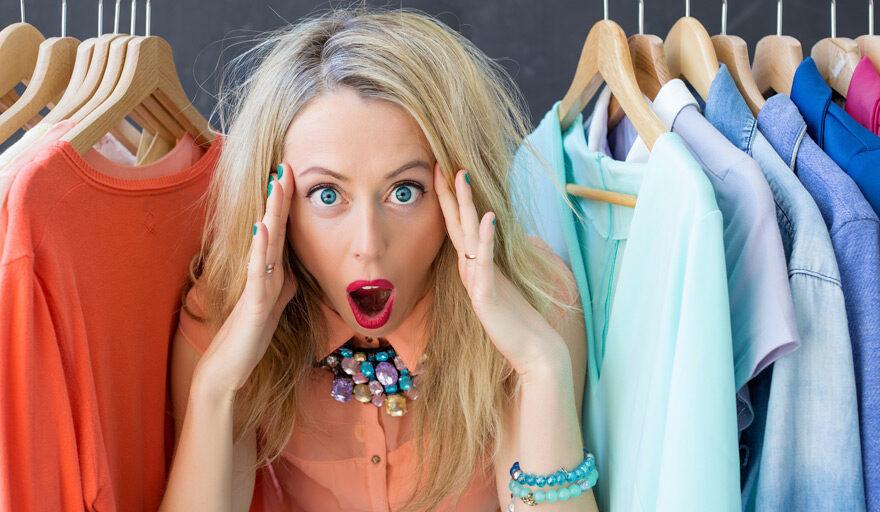 Women standing between hanging clothes in her closet looking stressed.