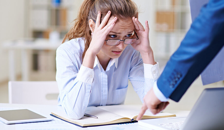 Woman taking criticism from someone else and looking stressed.