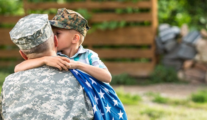 Boy kissing his dad on the cheek after coming home from the military.