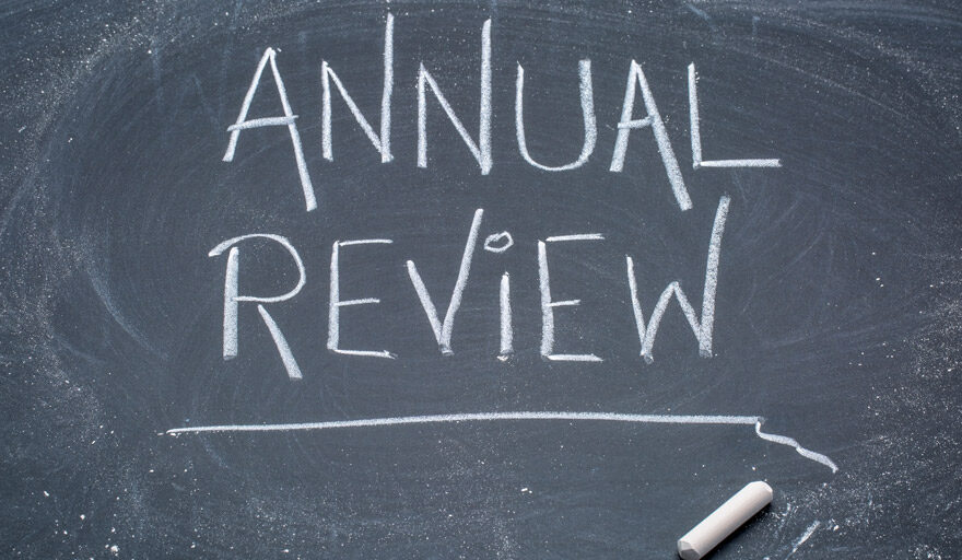 """Black board with the words """"annual review"""" written out"""