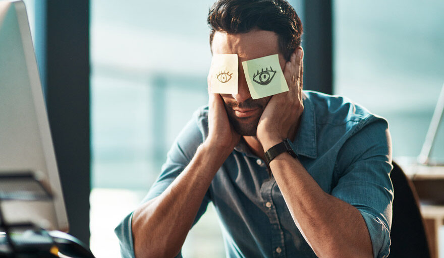Man with post-it notes that have drawn on eyes placed over his eyes