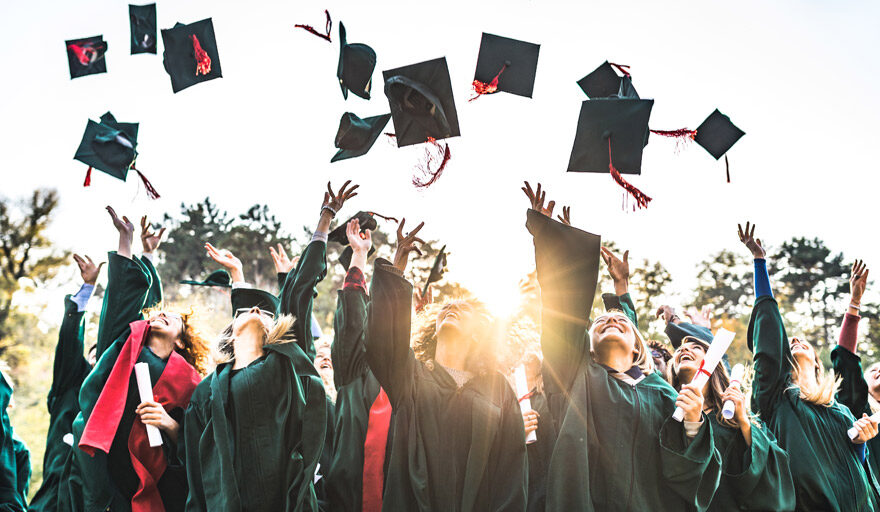 Graduation class throwing their caps in the air