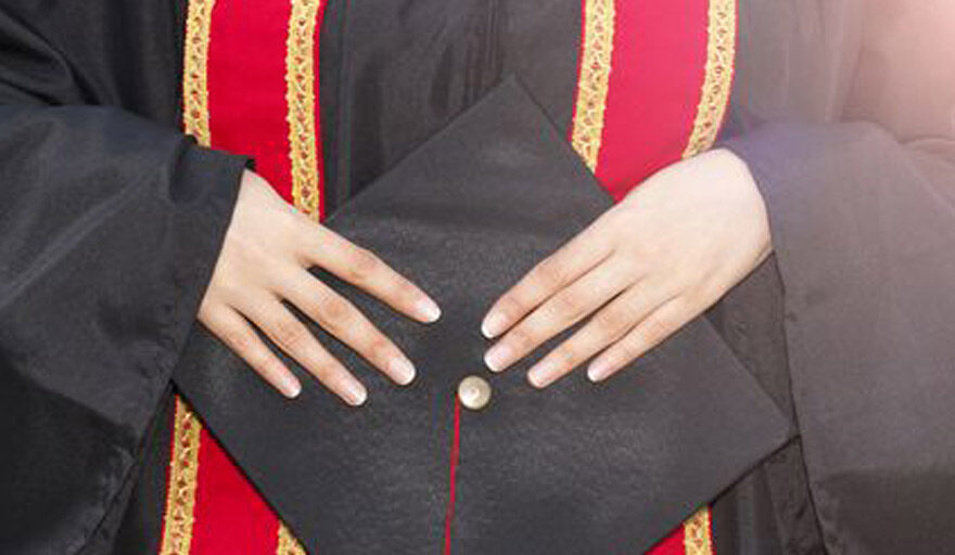 A person who is graduating holding their cap in their hands