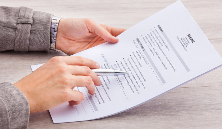 Person pointing to a resume with a pen