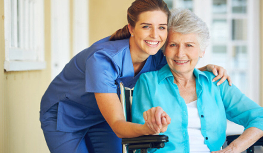 Healthcare worker hugging woman in wheelchair