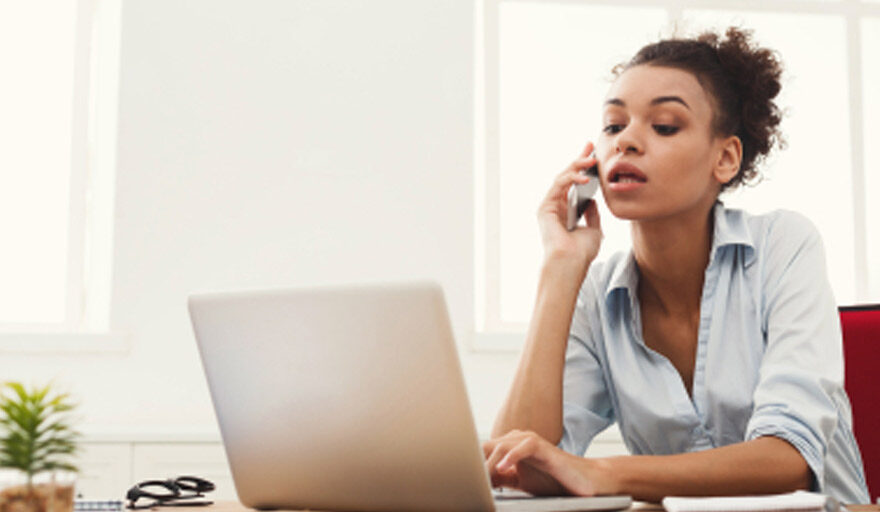 Woman on phone while working on laptop