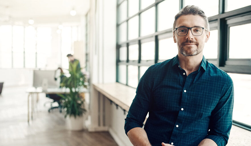Man leaning against standing desk looking at camera
