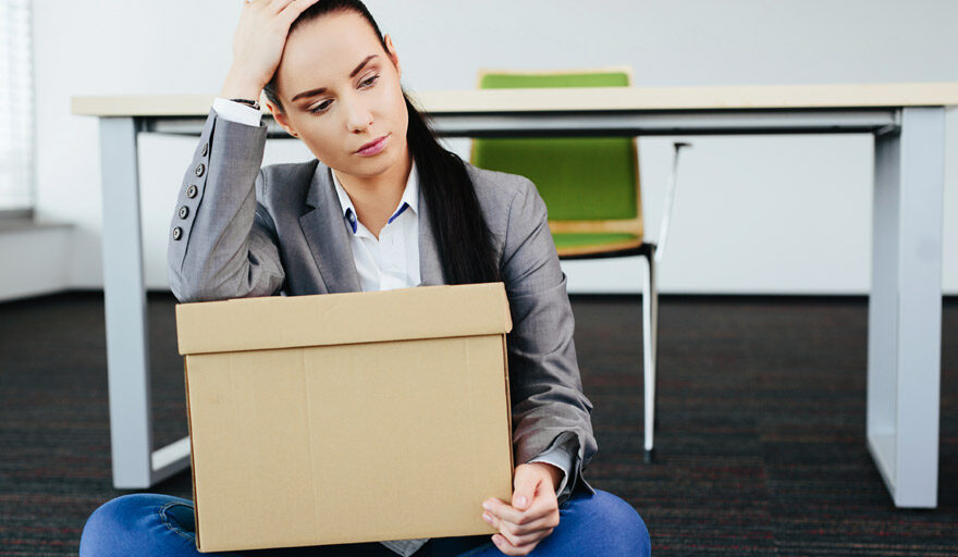 Woman sitting on ground looking disappointed with box in her lap