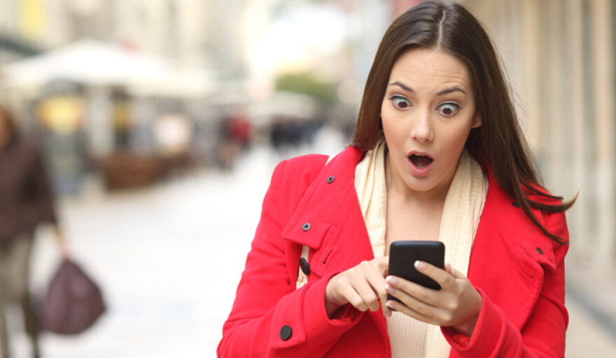 Women looking at phone surprised.