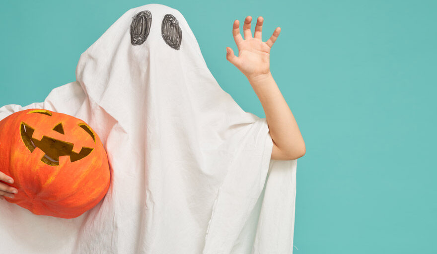 Person in ghost costume holding a pumpkin