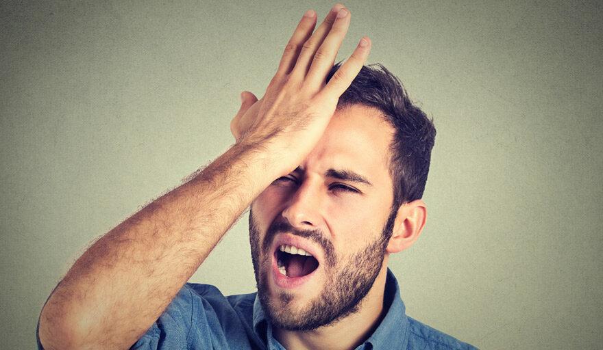 Man hitting palm against his head