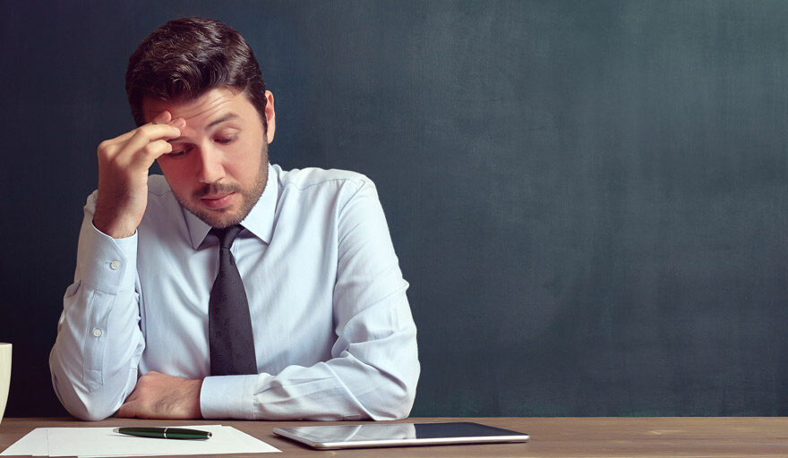 Man staring at paper looking concerned