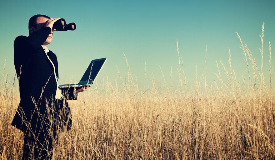 Man in field looking through binoculars