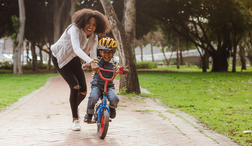 Mom helping her son ride a bike