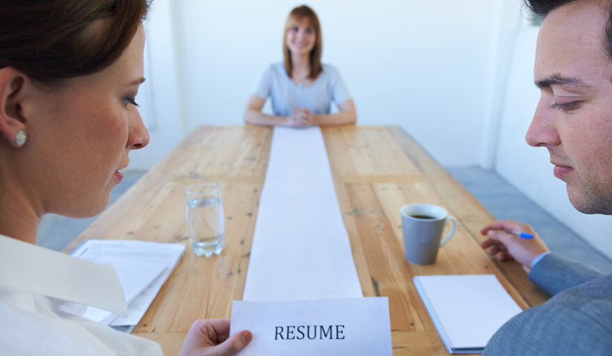 2 people sitting at the end of the table holding an extremely long resume page