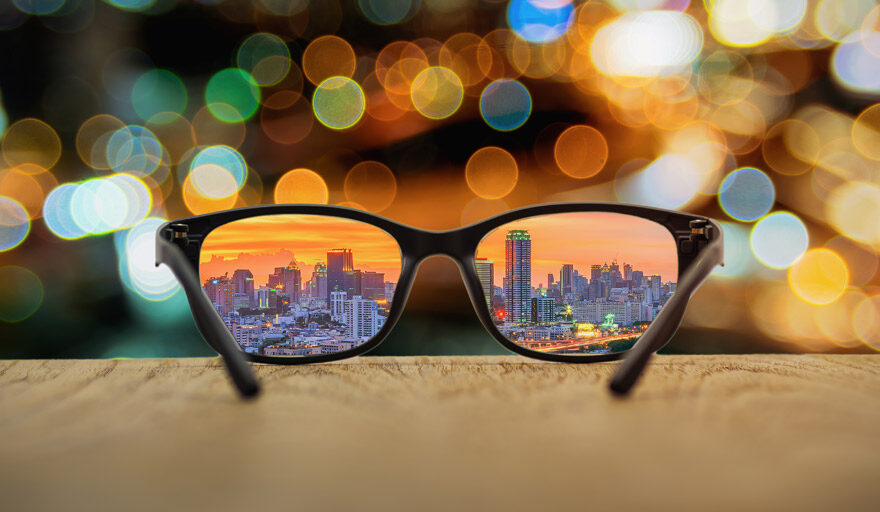 A pair of glasses with the city shining through