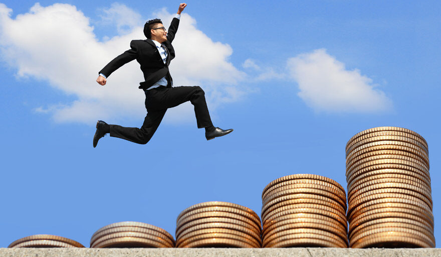 Man jumping over giant coin piles