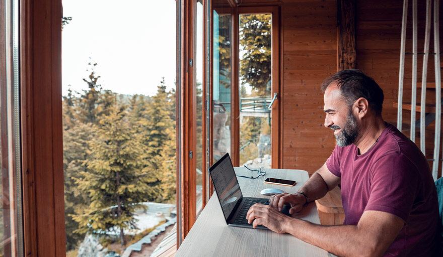 Man working on laptop in cabin
